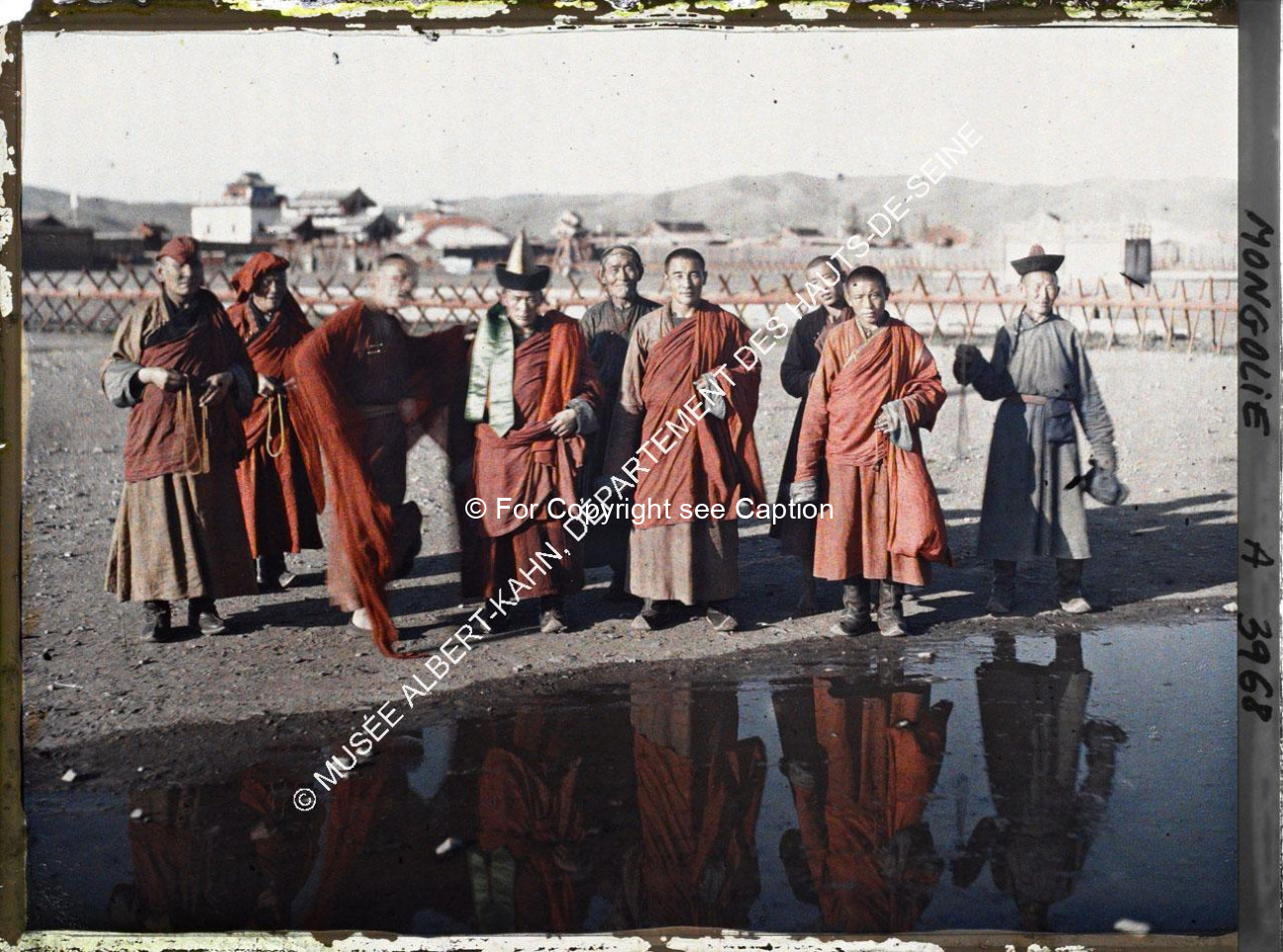 Monks and laymen in front of the Yellow Palace and the Eastern part of Züün khüree with a chanting m